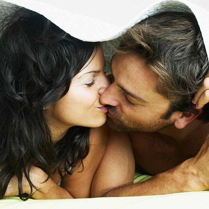 couple-kissing-under-blanket